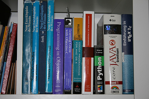 Programming books and documentation on shelf